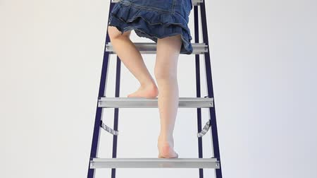 small height : Little girl climbs down from a stepladder Stock Footage