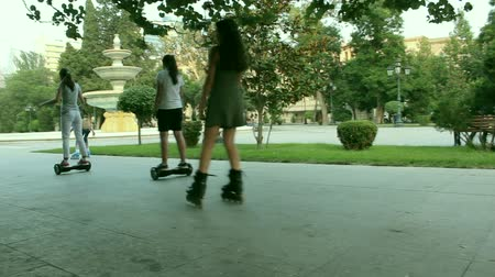 two wheeled : Children riding self-balancing scooter and roller skate in a park Stock Footage