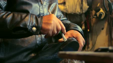 lehúzó : Shoe maker is repairing a shoe sticking it with glue at his old atelier.