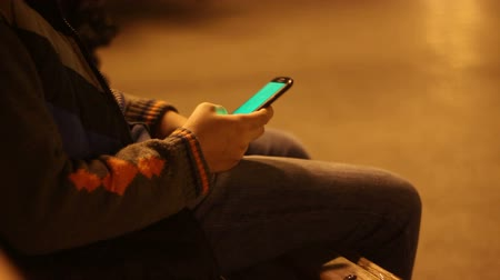 boyish : Young boy with smartphone in a city park at night