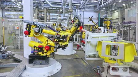 robots : robotic arms in a car factory