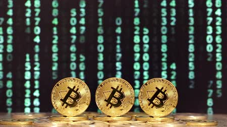 data mining : three bitcoins with sequence of changing green numbers in background
