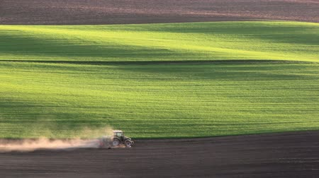 Богемия : Sunset light over cultivating tractor in the spring, South Moravia, Czech Republic