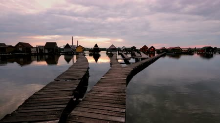 fishing village : Sunset over lake Bokod with wooden pier and floating houses, power plant in background, Hungary Stock Footage