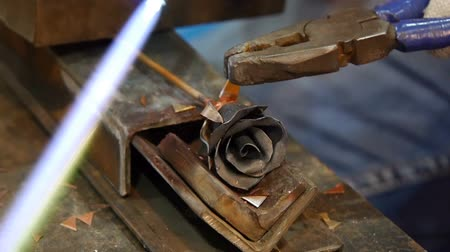 forging sword : The blacksmith makes a metal rose. Melts a flower petal. Pliers bends the sheet. Stock Footage