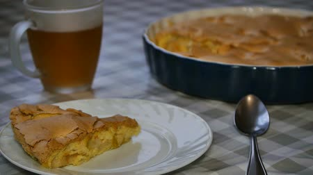 charlotte pie : The woman put a slice of homemade apple pie on a plate. Apple pie and a cup of hot tea.