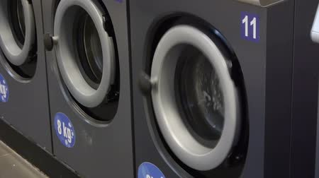 front door : Video of self-service laundry - coin laundrywashing machines and colourful laundry. Close-up. Stock Footage