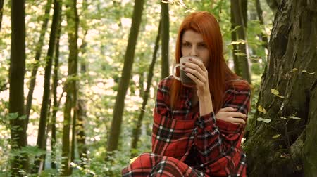 knitted gloves : Young woman in a park or in the forest drinking coffee or tea from a cup. Stock Footage