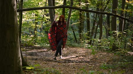 knitted gloves : Young girl wrapped in a plaid. Walking alone at forest. the overall plan.