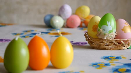 Candles made in shape of easter egg. Green, orange, yellow. Easter eggs candles and colorful Easter eggs in the background.