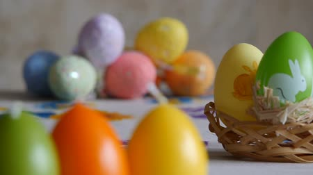Close-up. Candles made in shape of easter egg. Easter eggs candles and colorful Easter eggs in the background. Refocusing. Stok Video