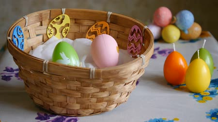 Colorful Easter Eggs green, yellow and pink In A Basket. Male hand adds one pink and one yellow Easter egg. Stok Video