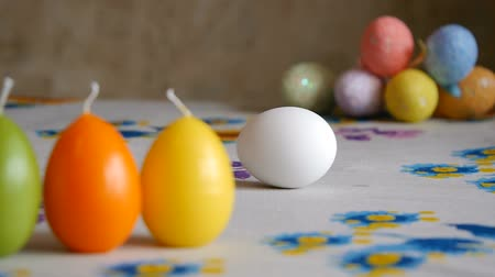 Easter. Female hand spin white egg on the table. Colorful Easter eggs in the background. Stok Video