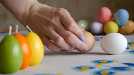 Happy Easter. Female hand putting on the table two easter eggs. colorful candles and colorful Easter eggs in the background. Stok Video