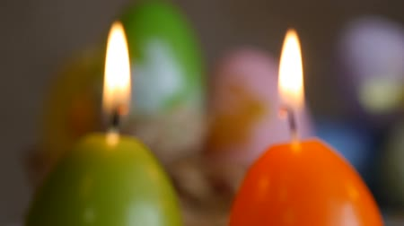Candles made in shape of easter egg. Green, orange, yellow. Easter eggs candles and colorful Easter eggs in the background. Focus and refocusing.