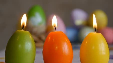 Candles made in shape of easter egg. Burning candles. Green, orange, yellow. Easter eggs candles and colorful Easter eggs in the background. Stok Video