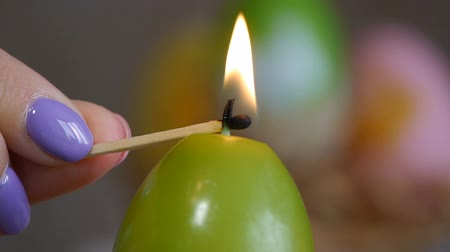 Candles made in shape of easter egg. Green candles. Female hand lights candles. Stok Video
