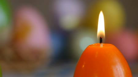 корзина : Candles made in shape of easter egg. Burning candles. Green, orange, yellow. Sliding, close-up.