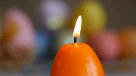 Candles made in shape of easter egg. Burning candles. Green and orange candles . Sliding, close-up. Orange candles extinguished from the air. Stok Video
