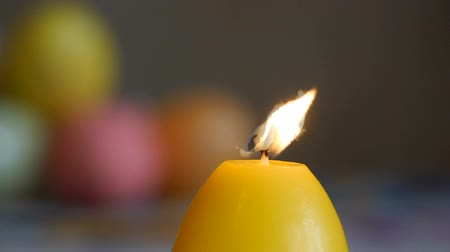 Candles made in shape of easter egg. Burning candles. Yellow candles extinguished from the air. Stok Video