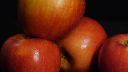 Juicy red apples isolated on a black background. Close up. Delicious fruit. Stok Video