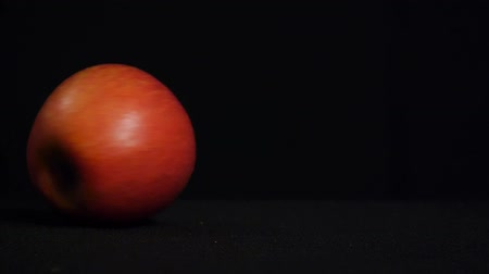 Close-up. Delicious juicy apple spins on a black background