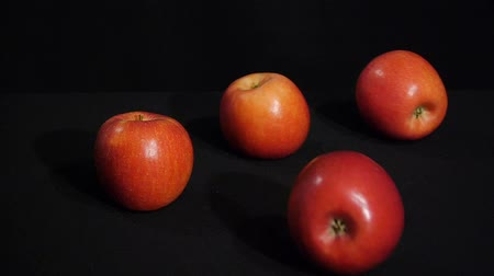 Beautiful red apples rolling on a black background. Juicy fruits.
