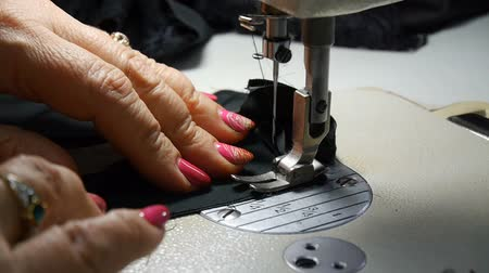 Close-up. Woman hands working with sewing machine. Factory textile sewing.