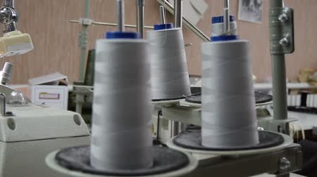 A spool of high quality grey cotton thread on a sewing machine spindle on foreground, close-up. Garment factory. Stok Video