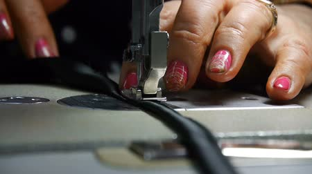 Closeup of tailor. Female hands of a seamstress at work. Sewing with a sewing machine with black material. Fashion industry. Stok Video