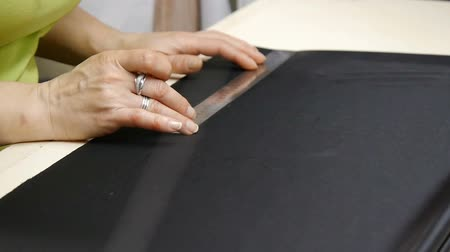 Female hands of a seamstress at work. A dressmaker cutting a high quality fabric black, before you sew it and make a piece of high fashion clothing. Traditional concept, industry and fashion.