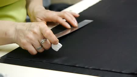 A dressmaker cutting a high quality fabric black, before you sew it and make a piece of high fashion clothing. Female hands of a seamstress at work. Traditional concept, industry and fashion.