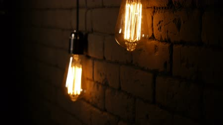 filaman : Vintage filament Edison light bulb. The lamps lights up in the dark. The incandescent lamp with a tungsten filament wobbles. The light flashes. Slow motion upwards.