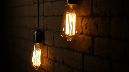 filaman : Vintage filament Edison light bulb. The lamps lights up in the dark. The incandescent lamp with a tungsten filament wobbles. The light flashes. Close up.