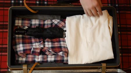 stuff bag : Man hands packing suitcase for travel. Top view. Flannel shirt, jeans, electric razor and other accessories for hipsters. Stock Footage