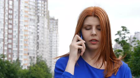 Young beautiful girl with red hair is seriously talking on a mobile phone.