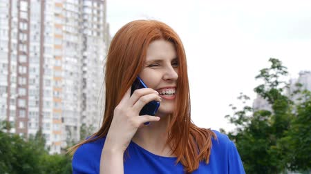 Young beautiful girl with red hair in the city talking on a mobile phone and smiles.