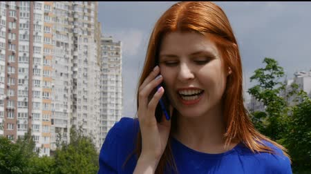 Young beautiful girl with red hair talking on a mobile phone and smiles. Very happy in the city.