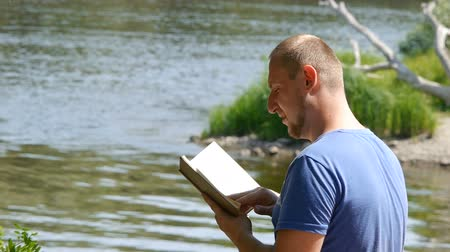 Young student reads a book on a river bank. Tourist with a book in nature.