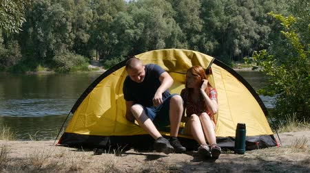 Concept of tourism and travel. Young happy couple sitting in tent watching the view. The beautiful nature surrounds young people. Drinking a tea. Forest and river on the background. Stok Video