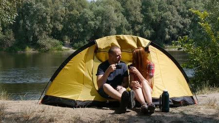 Concept of tourism and travel. Young happy couple sitting in tent watching the view. Drinking a tea, laugh and talk. Forest and river on the background.