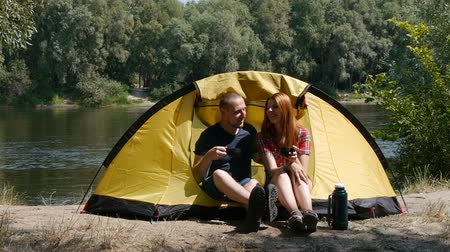 Young happy couple sitting in tent watching the view. Drinking a tea, laugh and talk. Forest and river on the background.