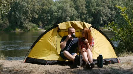 Young happy couple sitting in tent watching the view. Drinking a tea, laugh and talk. Forest and river on the background. Concept of tourism and travel.