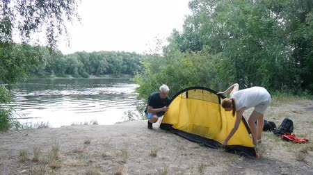 Father and daughter campers putting up tent. Green tourism, hiking. Happy travels concept.