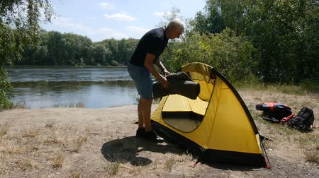 Elderly male retired tourist put a sleeping bag in the tent. Green tourism, hiking.