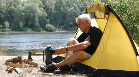 Senior old man hiker, more than 50 years old sitting in a tent. Camper man drinking coffee or tea. River and forest in the background. Relaxation, travel, green tourism concept. Stok Video
