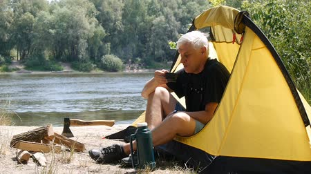 Hiker sitting in a tent. Camper man drinking coffee or tea. River and forest in the background. Relaxation, travel, green tourism concept. Stok Video