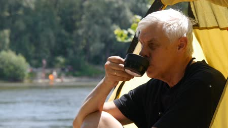 Elderly gray haired camper man sitting in the tent, drinking tea. Close up. River and forest in the background. Hiking, travel, green tourism concept.