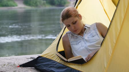 Hiker girl reads book in camping tent. People living healthy active lifestyle. River and forest in the background. Hiking, travel, green tourism concept.