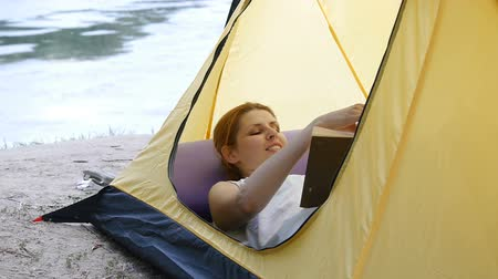 Young woman resting and reading book in a tent on the nature. River in the background. Hiking, travel, green tourism concept. Healthy active lifestyle. Stok Video